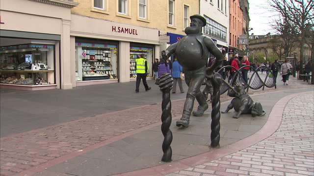 stockvideo's en b-roll-footage met exterior shots of dundee city centre street scenes, a statue of desperate dan and his dawg, a statue of minnie the minx and caird hall on may 1, 2015... - geboren in