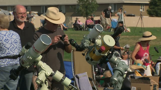 exterior shots of eclipse watchers looking through telescopes and eclipse glasses and shots filmed through a filter as the moon's shadow begins to... - solar eclipse glasses stock videos and b-roll footage