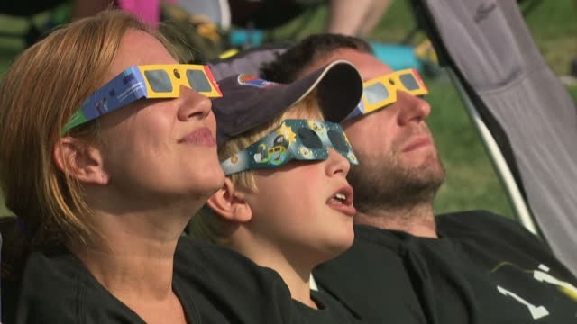 exterior shots of eclipse watchers looking through telescopes and eclipse glasses and shots filmed through a filter as the moon's shadow passes... - atmosphere filter stock videos and b-roll footage