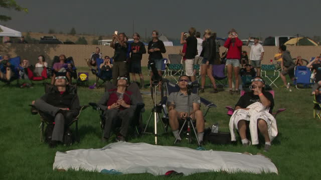 exterior shots of eclipse watchers viewing the total solar eclipse through eclipse glasses and people cheering as the sky darkens during the moment... - solar eclipse glasses stock videos and b-roll footage