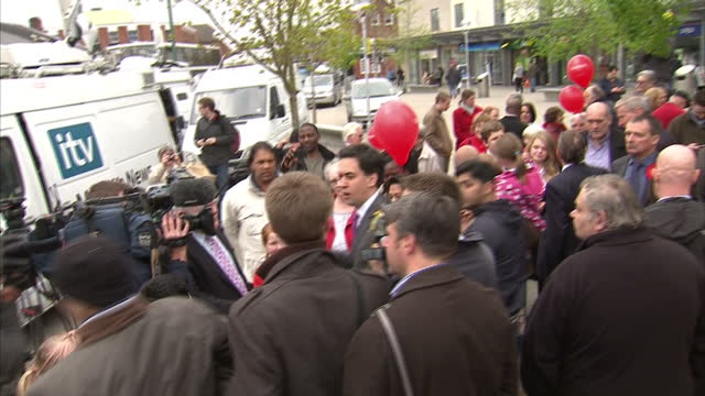 exterior shots of ed miliband speaking to press and media as man in black hat leans over and cracks egg on shoulder of miliband before he runs off... - ed miliband stock-videos und b-roll-filmmaterial