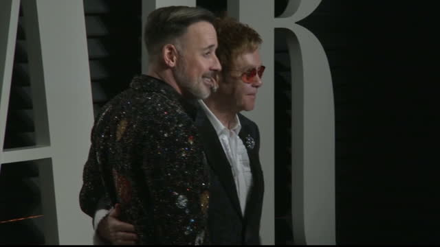 Exterior shots of Elton John and his husband David Furnish arriving at the Vanity Fair Oscar Party on February 27 2017 in Los Angeles California
