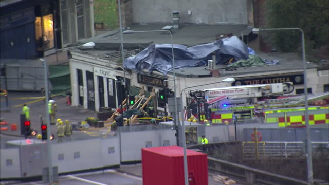 exterior shots of emergency services outside the clutha pub with a tarpaulin covering the wreckage of a crashed police helicopter on the roof and... - ヘリコプター事故点の映像素材/bロール