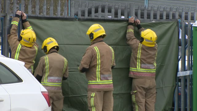 exterior shots of emergency workers fire fighters putting up a green protective sheet on gates of the ashley wood garage at churchfield industrial... - protective sheet stock videos and b-roll footage