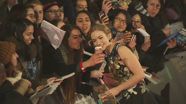 Exterior shots of Emily Blunt posing for selfie photos with fans and signing autographs with husband John Krasinski actor by her side on the red...
