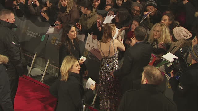Exterior shots of Emma Stone signing autographs for fans on the red carpet at the BAFTA Awards at the Royal Albert Hall on February 12th 2017 in...