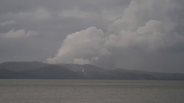 exterior shots of empty small boats with taal volcano spewing smoke and ash in a background on 15 january 2020 in laurel in batangas province... - taal volcano stock videos & royalty-free footage