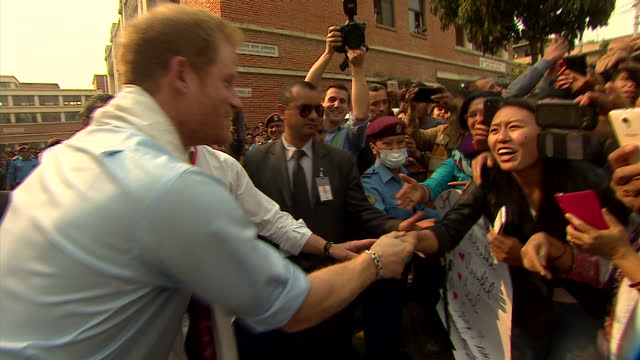 Exterior shots of enthusiastic members of the public outside Kanti Children's Hospital and Prince Harry stopping to greet some of them as he departs...