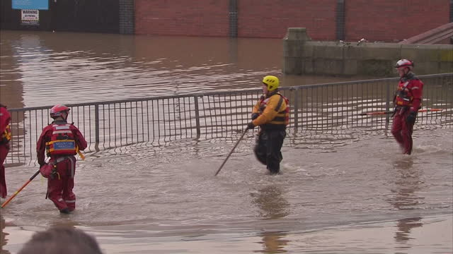 Exterior shots of Environment Agency staff in a boat and Mountain Rescue workers wading through flood waters during flood relief efforts in York>> on...