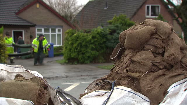 vídeos de stock, filmes e b-roll de exterior shots of environment agency workers helping in flood clear up shots of sandbags at front doors and shots of damaged belongings in front of... - lancashire