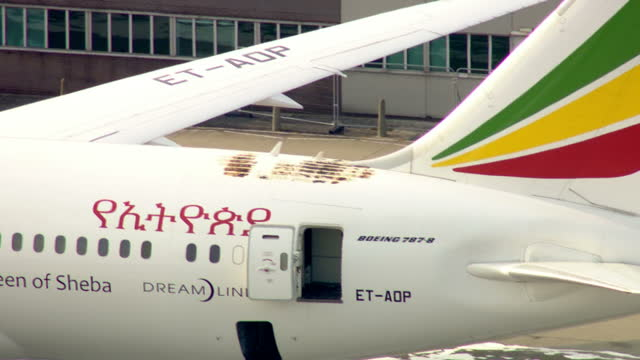 exterior shots of ethiopian airlines boeing 787 dreamliner on tarmac of heathrow airport with fire engines surrounding it and hole in roof where fire... - boeing 787 stock videos and b-roll footage