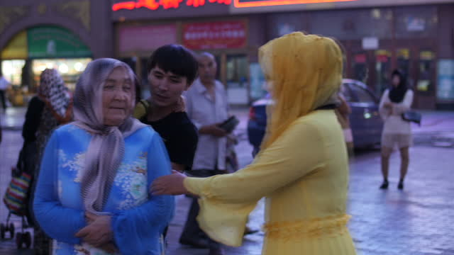exterior shots of ethnic minority muslims going about their daily lives in a bustling marketplace in urumqi xinjiang province on august 25 2014 in... - xinjiang province stock videos & royalty-free footage
