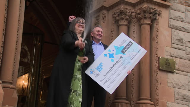 exterior shots of euromillions lottery winners frances and patrick connelly from county armagh spraying champagne and posing with a large... - 宝くじ点の映像素材/bロール