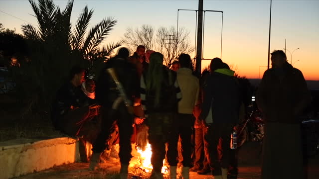 Exterior shots of evacuees from Eastern Aleppo gathered in winter coats with belongings around a fire on December 16 2016 in Aleppo Syria