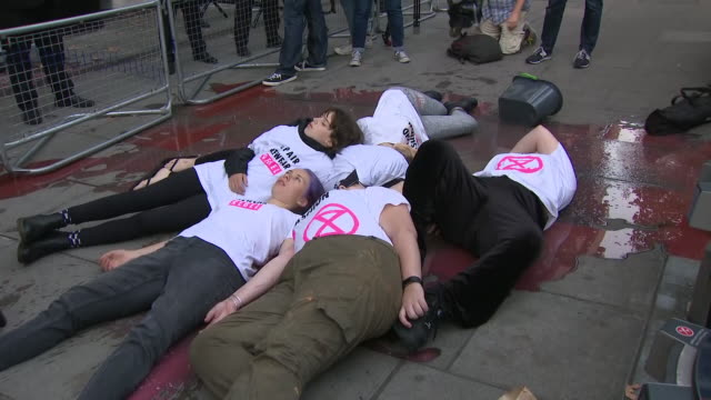 exterior shots of extinction rebellion protesters daubed in fake blood and lying on ground outside a london fashion week venue women are glued to... - fashion industry stock videos & royalty-free footage