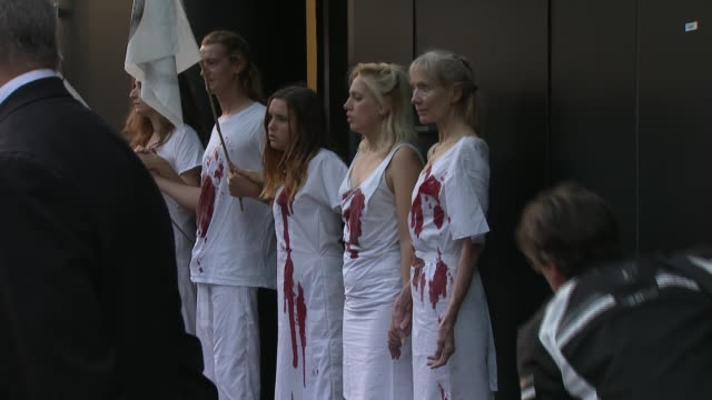 exterior shots of extinction rebellion protesters daubed in fake blood and lying on ground outside a london fashion week venue women are glued to... - fashion week stock videos & royalty-free footage