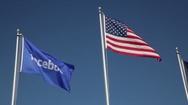 Exterior shots of Facebooks Data Center Prineville Oregon US Shots of a Facebook flag flying beside an American flag on flagpoles above the Facebook...
