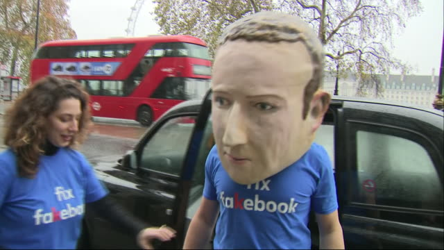 exterior shots of fake mark zeckerberg in paper mache head mask arriving in taxi for fake news inquiry holding a 'where is mark?' sign as part of the... - imitation stock videos & royalty-free footage