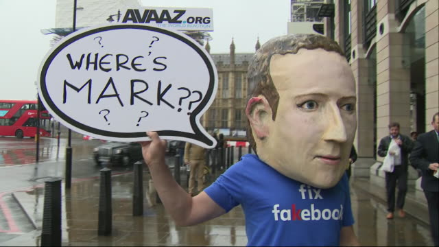 exterior shots of fake mark zeckerberg in paper mache head mask in front of parliament holding a 'where is mark' sign as part of the protest pressure... - 人工的点の映像素材/bロール