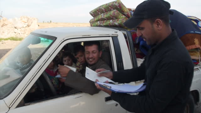 Exterior shots of families in trucks and cars with belongings being stopped and paperwork checked by Iraqi military troops on March 17 2015 in Tikrit...