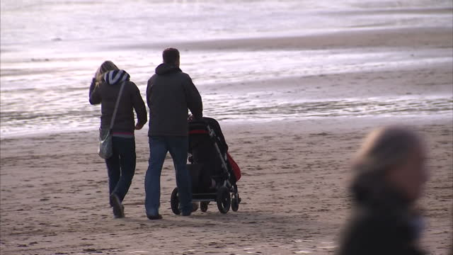 Exterior shots of families walking on beach on sunny New Year's Day including shots of anonymous shots of parents with children and pushing pram and...