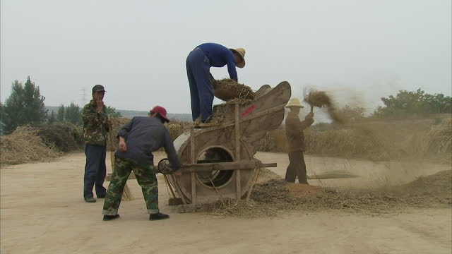 exterior shots of farmers using a handcranked threshing machine to separate grain from stalks and chaff rural chinese village and agriculture scenes... - threshing stock videos & royalty-free footage