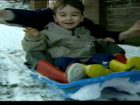 exterior shots of father pulling children along in sled exterior shots man clearing driveway from snow exterior shots train tracks covered in snow - 水の形態点の映像素材/bロール