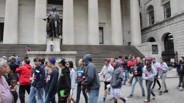exterior shots of federal hall on wall street in lower manhattan as commuters and tourists walk around the statue of george washington tourists pose... - george washington portrait stock videos and b-roll footage