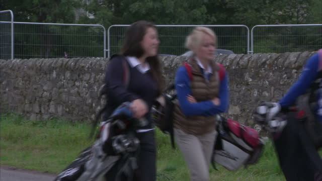 exterior shots of female golfers walking with golf bags and golf clubs. on september 18, 2014 in st andrews, scotland. - st. andrews scotland stock videos & royalty-free footage