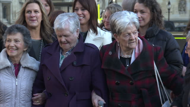 exterior shots of female protesters holding placards for equal pay some with grazia magazine branding outside the house of commons on december 16... - uguaglianza video stock e b–roll