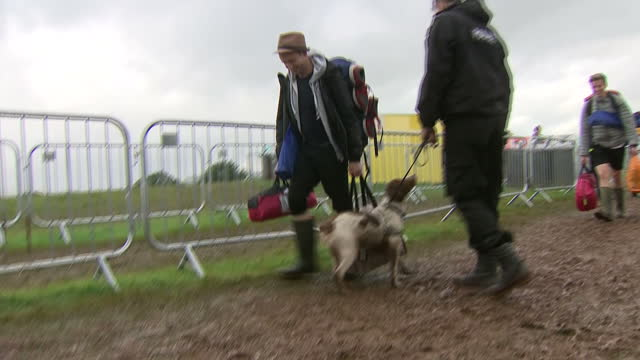 stockvideo's en b-roll-footage met exterior shots of festival goers arriving at the kendal calling music festival, walking through the mud with their belongings as a policeman with a... - festivalganger