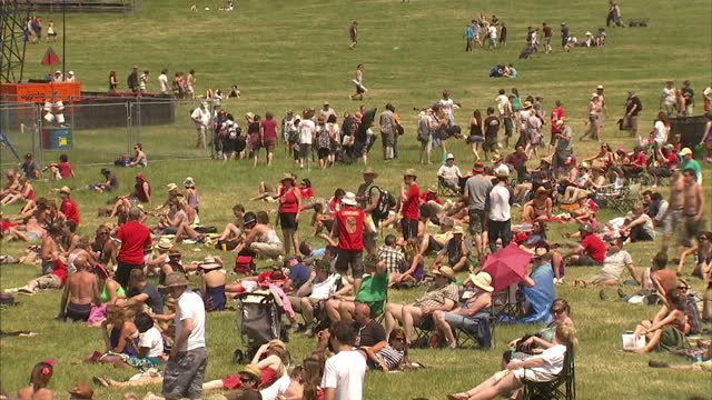 exterior shots of festivalgoers lounging in fields near the pyramid stage and walking across the festival grounds in hot sunny weather>> on june 23... - adagiarsi video stock e b–roll