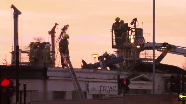 exterior shots of fire and rescue workers surveying the roof of the clutha pub and the wreckage of a police helicopter which crashed into the pub... - ヘリコプター事故点の映像素材/bロール