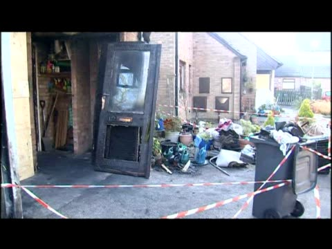 exterior shots of fire damaged house scene floral tributes
