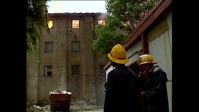 Exterior shots of firefighters attempting to put out fires during heavy fighting in May 1992 in Sarajevo Bosnia and Herzegovina