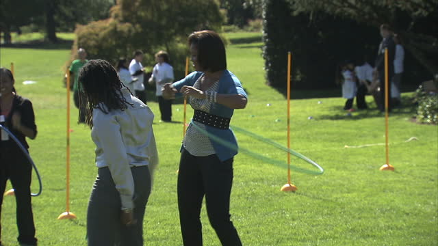 exterior shots of first lady michelle obama doing hula hoops with young children on the white house lawn at an event aimed at getting young people... - first lady stock-videos und b-roll-filmmaterial