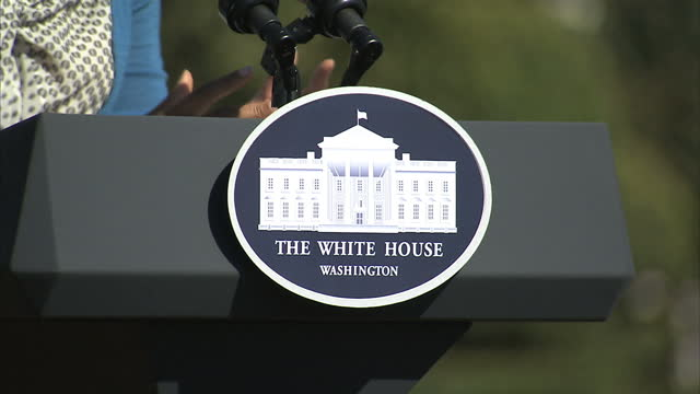 exterior shots of first lady michelle obama speaking at a podium on the white house lawn to an audience of young girls and assembled journalists on... - first lady stock-videos und b-roll-filmmaterial