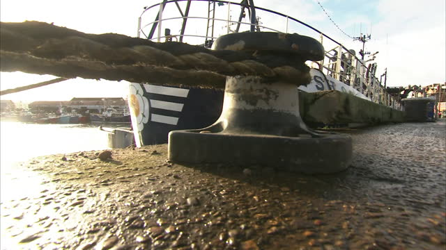 exterior shots of fishing boats docked at scarborough harbour on clear blue sunny day and fishing equipment piled up on the side of the docks on 27th... - sunny video stock e b–roll