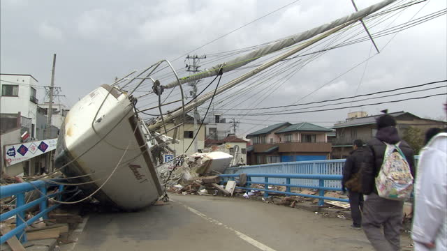 Exterior shots of fishing boats grounded on streets and damaged and completely destroyed buildings and cars after an earthquake tsunami hit the area...