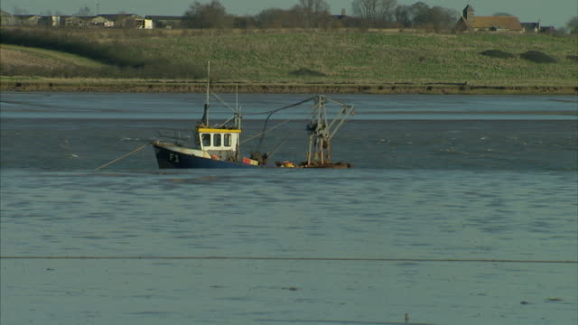 exterior shots of fishing boats moored on the swale estuary including shots of the coastal landscape and mudflats at low tide>> on january 15 2016 in... - landscape scenery点の映像素材/bロール