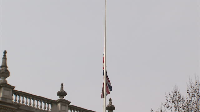 exterior shots of flag at half mast over downing street and crowds looking through gates. flag flying at half mast over downing street on april 08,... - ボブ・マーリー点の映像素材/bロール