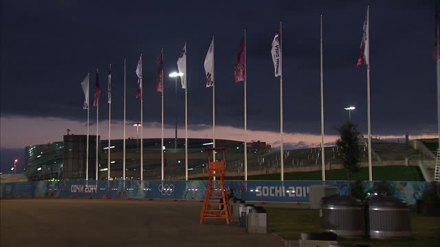 vídeos y material grabado en eventos de stock de exterior shots of flags flying at the sochi olympic park and the olympic park lit up at night>> on february 05 2014 in sochi russia - sochi