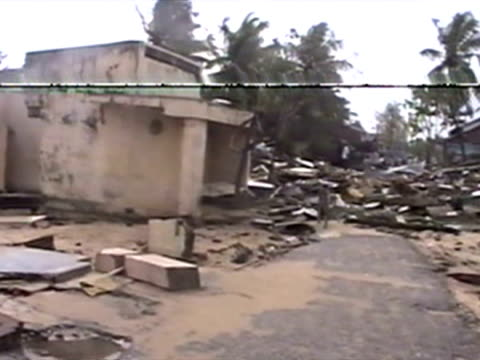 exterior shots of flattened buildings homes and houses next to beach front broken bits of wood concrete and flood water covering the streets and... - 2004年点の映像素材/bロール