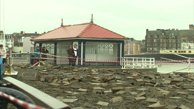 vídeos de stock, filmes e b-roll de exterior shots of flood damage along the aberystwyth seafront with paving stones gravel and debris scattered across the promenade and locals looking... - aberystwyth