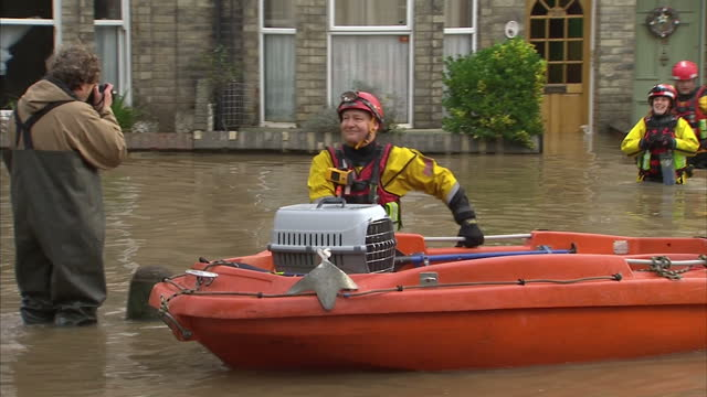 exterior shots of flood rescue workers handing over a cat in a pet carrier to its owners after rescuing it from a flooded home in york>> on december... - gabbietta per animali video stock e b–roll