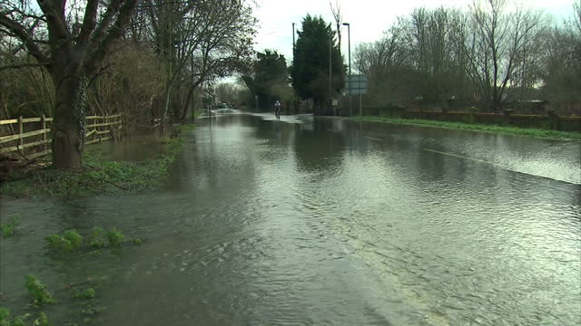 stockvideo's en b-roll-footage met exterior shots of flooded fields and a cordoned off street with a 'road closed' sign due to flooding. flood levels continue to rise along parts of... - bord weg afgesloten