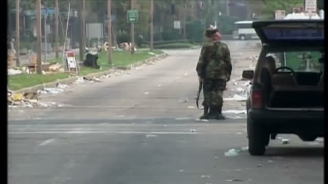 vidéos et rushes de exterior shots of flooded streets armed troops patrolling deserted streets after hurricane katrina hit the area on september 20 2005 in new orleans... - armement