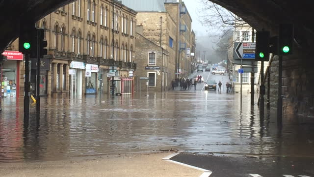 Exterior shots of flooding on streets in Hebden Bridge including shots of police and bystanders looking on as a bus is forced to turn around to avoid...