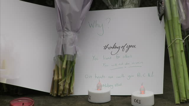 exterior shots of floral tributes laid at a war memorial for jo cox mp who was killed in her constituent outside a library filmed on june 16 2016 in... - murder stock videos & royalty-free footage