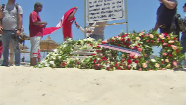exterior shots of floral tributes on a beach in sousse at the scene of the massacre, with an 'in memorium' plaque and people stood paying their... - 飾り板点の映像素材/bロール